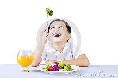 Happy boy with salad on white