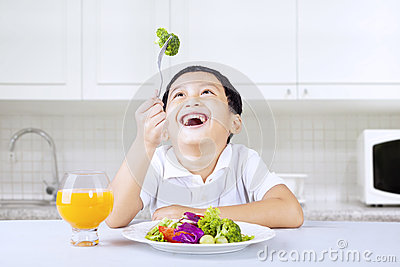 Boy laughing at green broccoli in kitchen