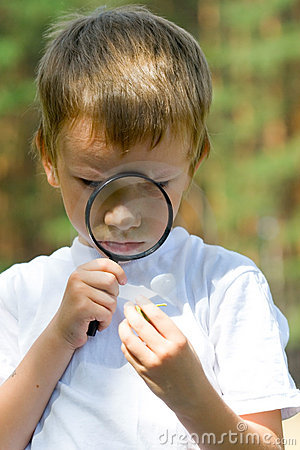 Happy boy with a magnifying glass