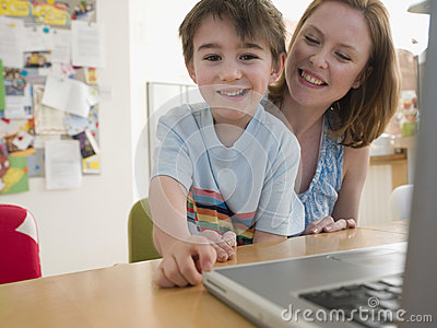Happy Boy And Mother With Laptop Sitting At Table