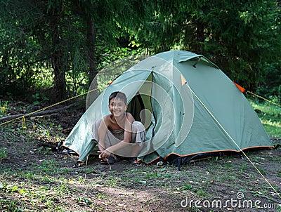 Happy boy near camping tent