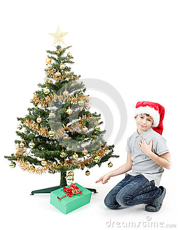 Happy boy in santa hat surprised by christmas present