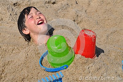 Happy Boy Under Sand