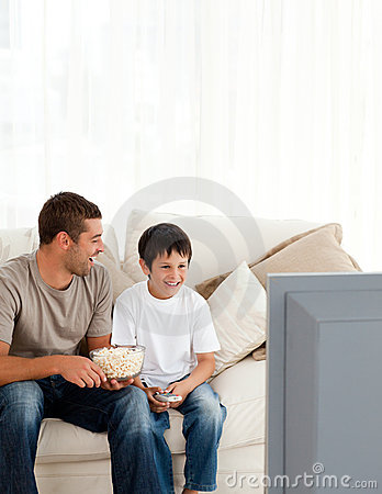 Happy boy watching tv with his father