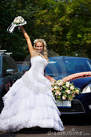 Happy bride with bouquet near wedding car