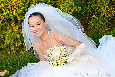 Happy bride with a flower bouquet in her hands