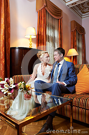 Happy bride and groom in interior of hotel room