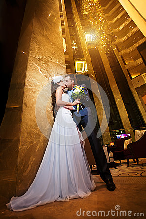 Happy bride and groom in the modern hotel hall
