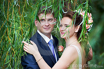 Happy bride and groom near willow tree