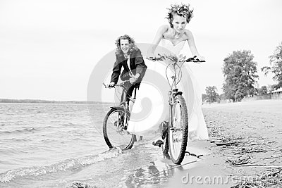 Happy bride and groom rides on bicycles
