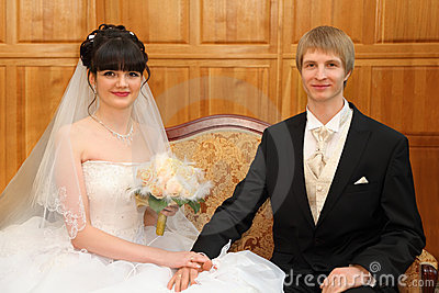 Happy bride and groom sit on couch