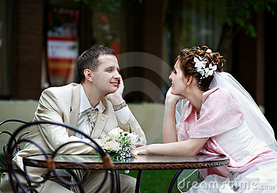 Happy bride and groom sit at table in cafe