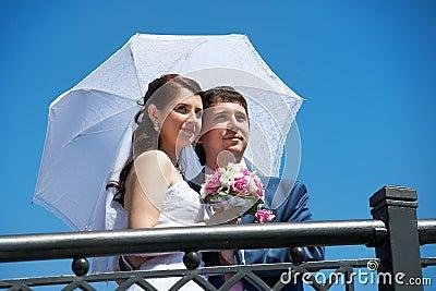 Happy bride and groom with umbrella