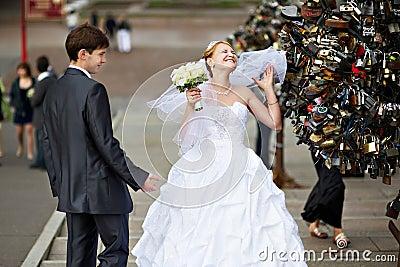 Happy bride and groom at wedding walk on bridge