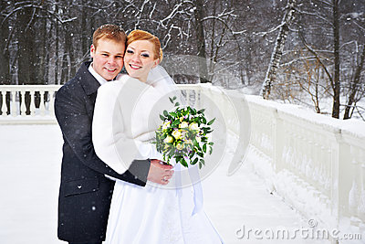 Happy bride and groom on winter park