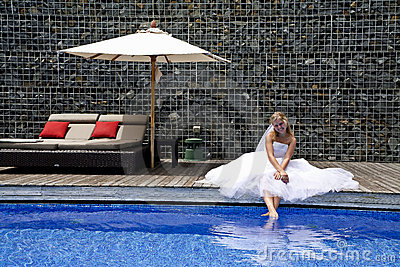 Happy bride near a pool