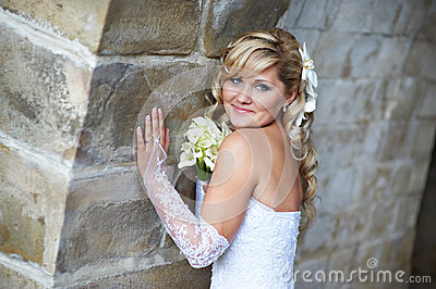 Happy bride near stone wall