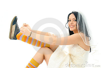 Happy bride putting on sporting shoes