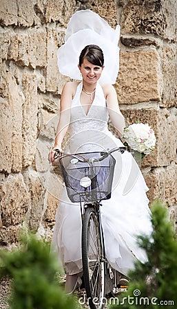 Happy bride riding a bike