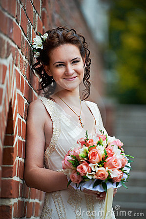 Happy bride with wedding bouquet about brick wall