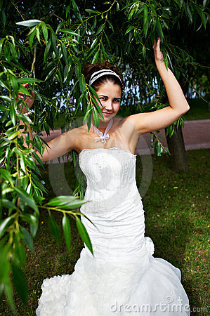 Happy bride in wedding dress and branch of tree