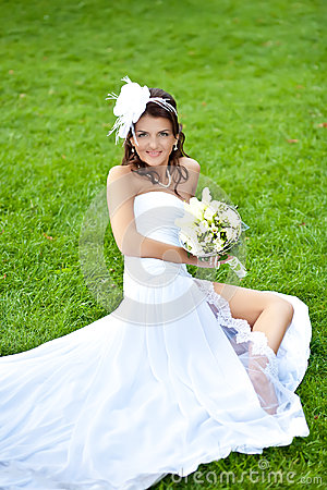 Happy bride in white dress siting on green grass