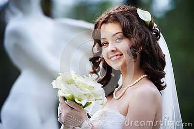 Happy bride with white wedding bouquet