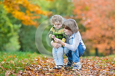 Happy brother and toddler sister in autumn park