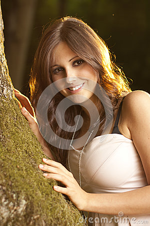 Happy brunet girl in a magic forest on moss