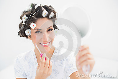 Happy brunette in hair rollers holding hand mirror and lip gloss