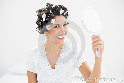 Happy brunette in hair rollers holding hand mirror smiling at ca