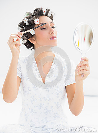Happy brunette in hair rollers looking in hand mirror and brushi