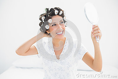 Happy brunette in hair rollers looking in hand mirror