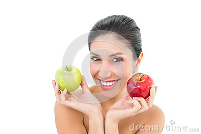 Happy brunette holding red and green apples and looking at camer