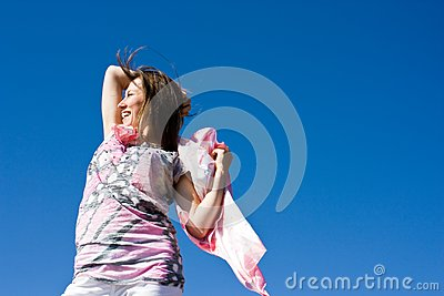Happy brunette playing with a scarf in the summer