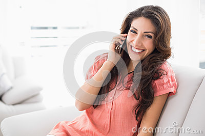 Happy brunette sitting on her couch on a phone call