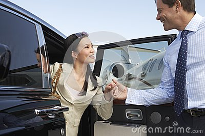 Happy Business Couple Getting Off A Car