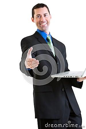 Happy business male on laptop gesturing handshake