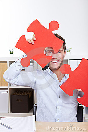 Happy business man with jigsaw