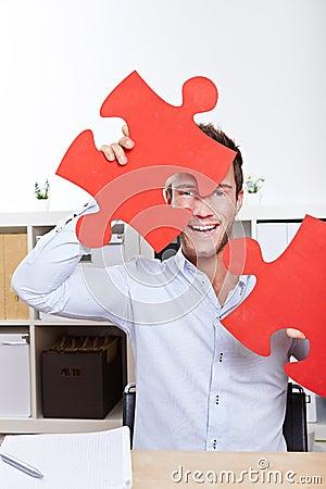 Happy business man with jigsaw