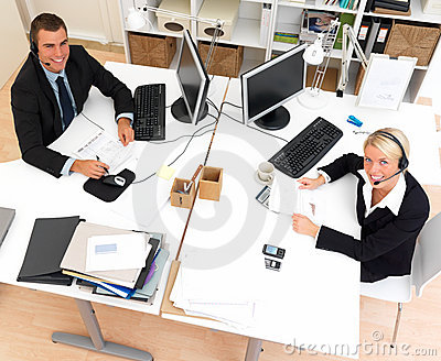 Happy business man and woman wearing headsets