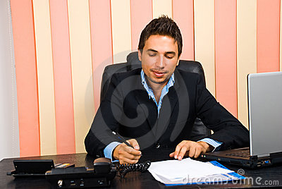 Happy business man write on paper in office