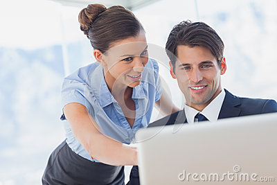 Happy business people looking together at the laptop