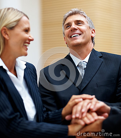 Happy business people with their hands together