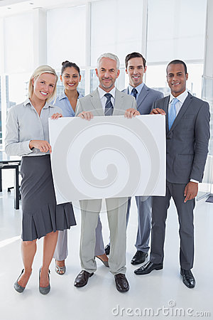 Happy business team holding large blank poster
