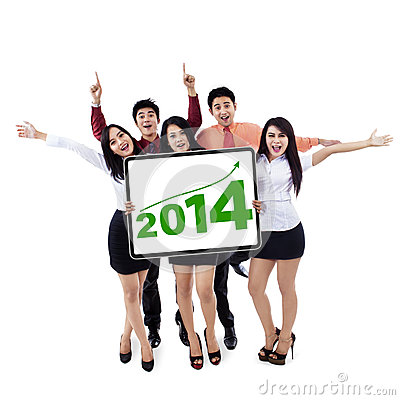 Happy business team showing the new year 2014