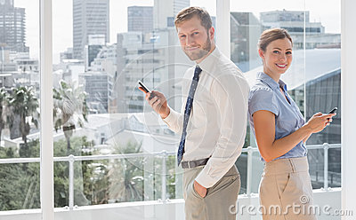 Happy business team standing back to back and texting