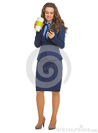 Happy business woman with cup of hot beverage writing sms