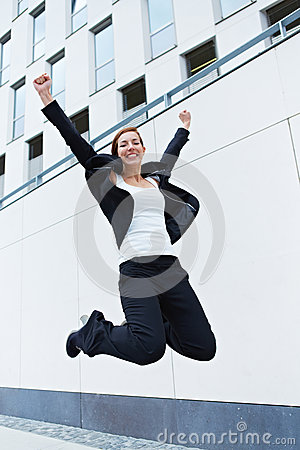 Happy business woman jumping into