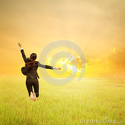 Happy business woman jumping in green rice field and sunset
